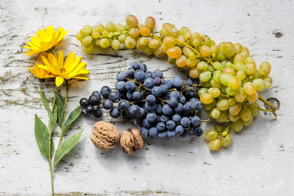 grapes by nut and daisy flower on table