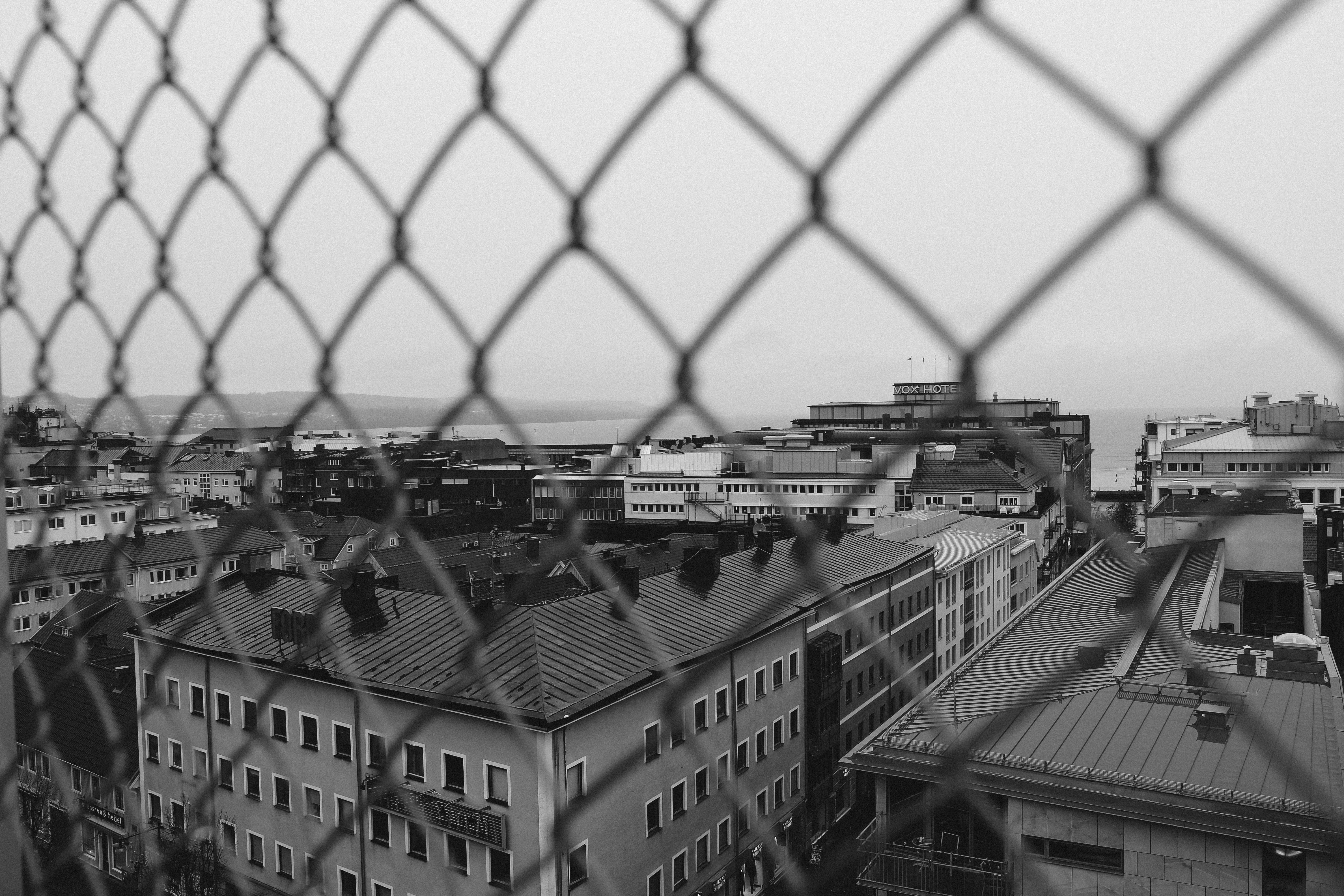 grayscale photo of chain link fence near buildings