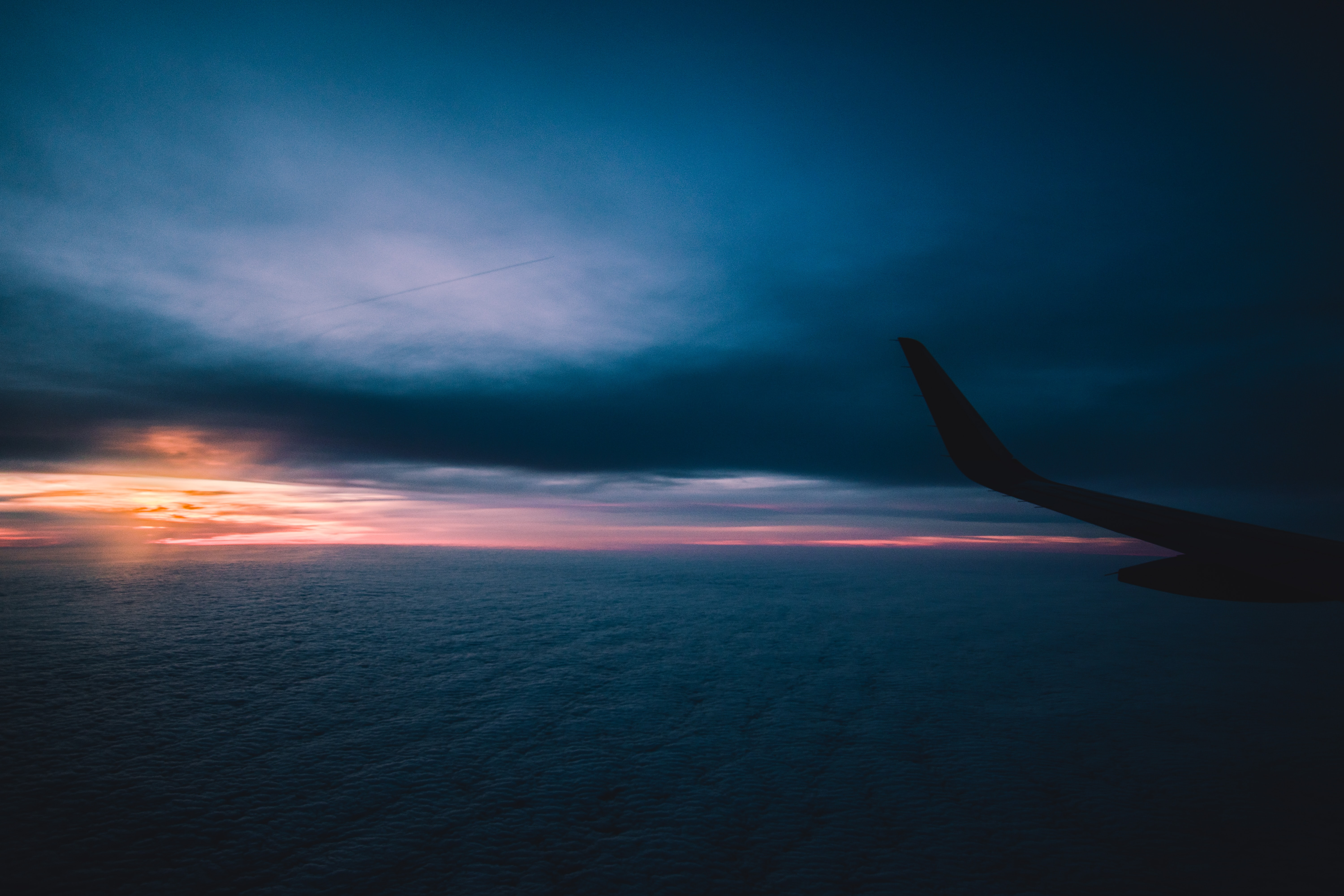 silhouette of airplane flying through sky