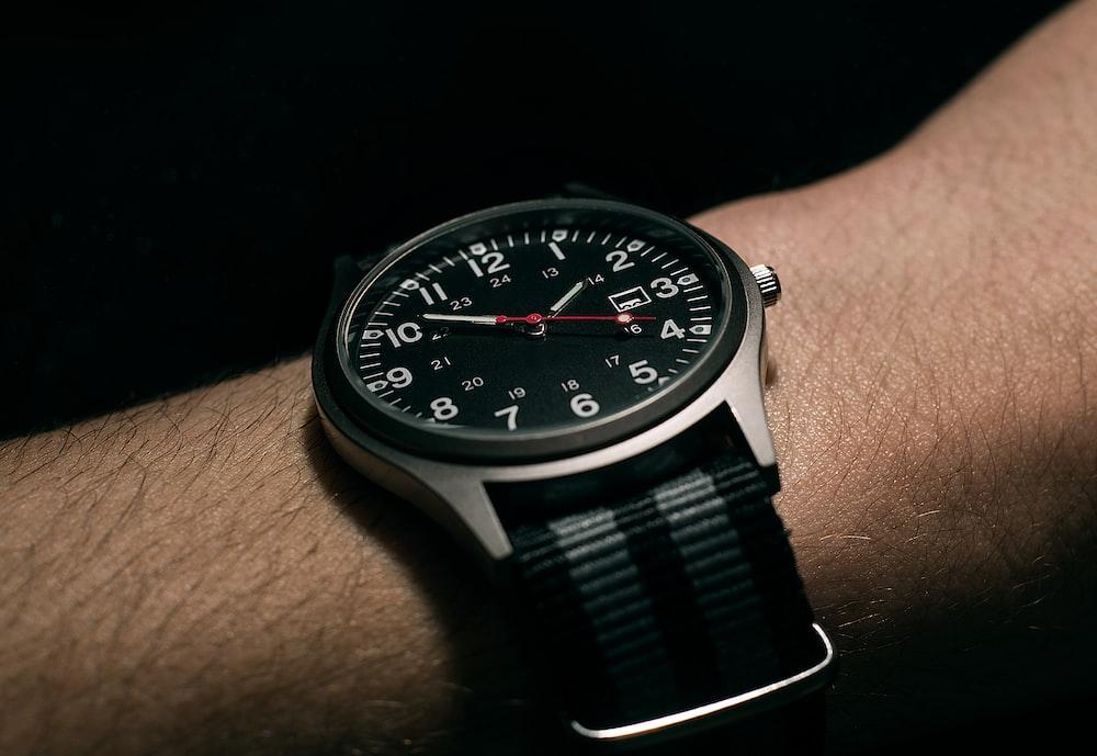 man wears black analog watch with black woven nylon strap