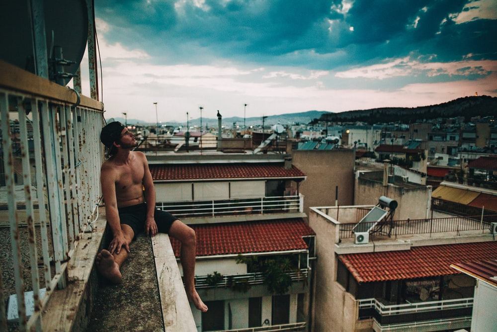 person sitting on the edge of building during daytime