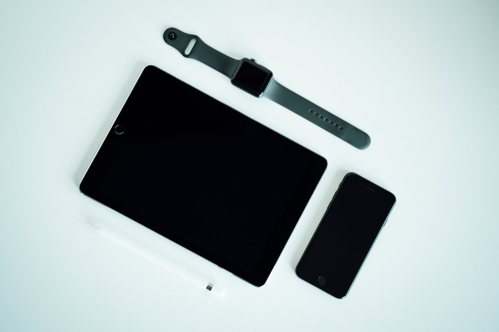 black iPad, post-2017 iPhone, and black aluminum case Apple Watch with gray Sport Band
