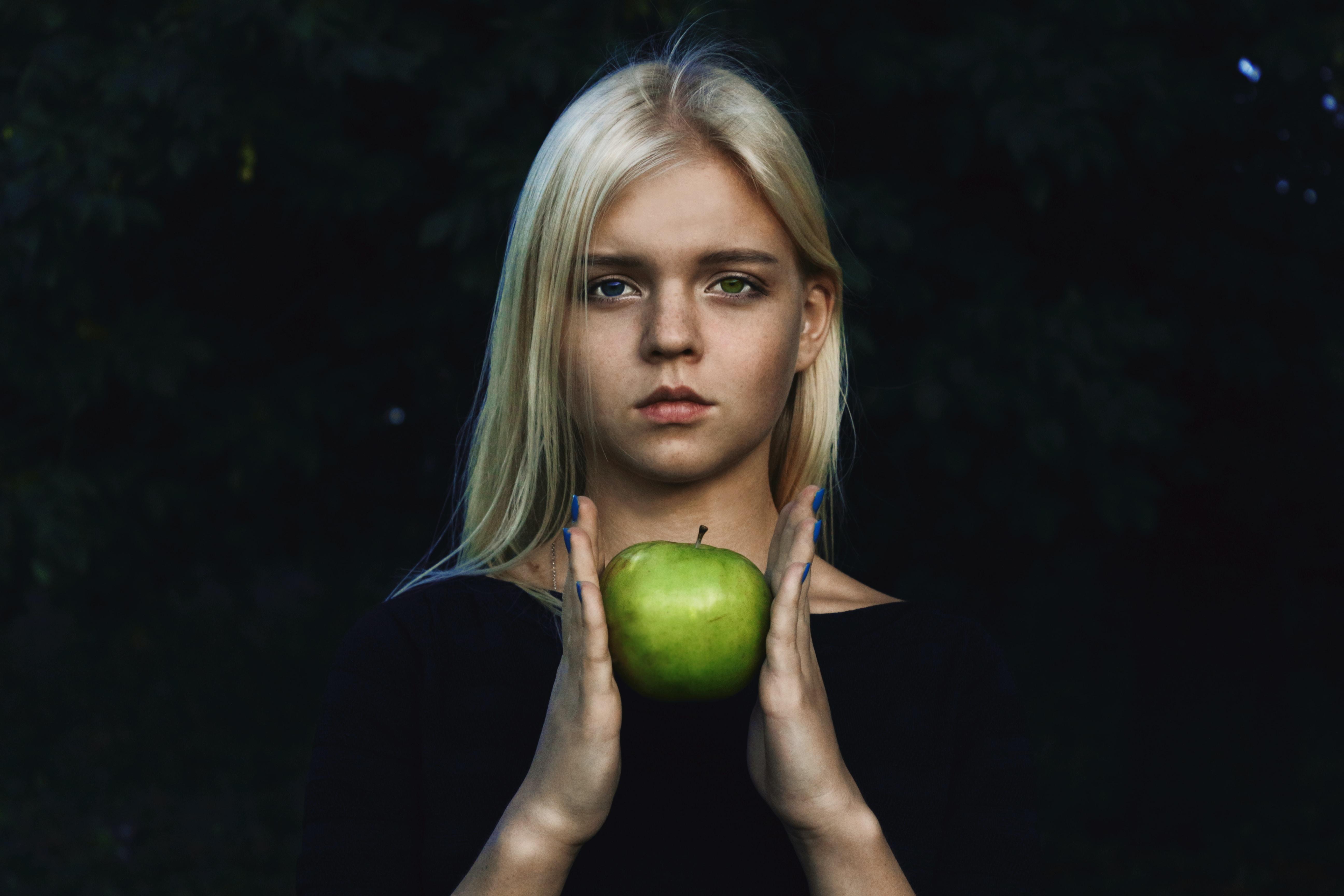 woman holding green apple