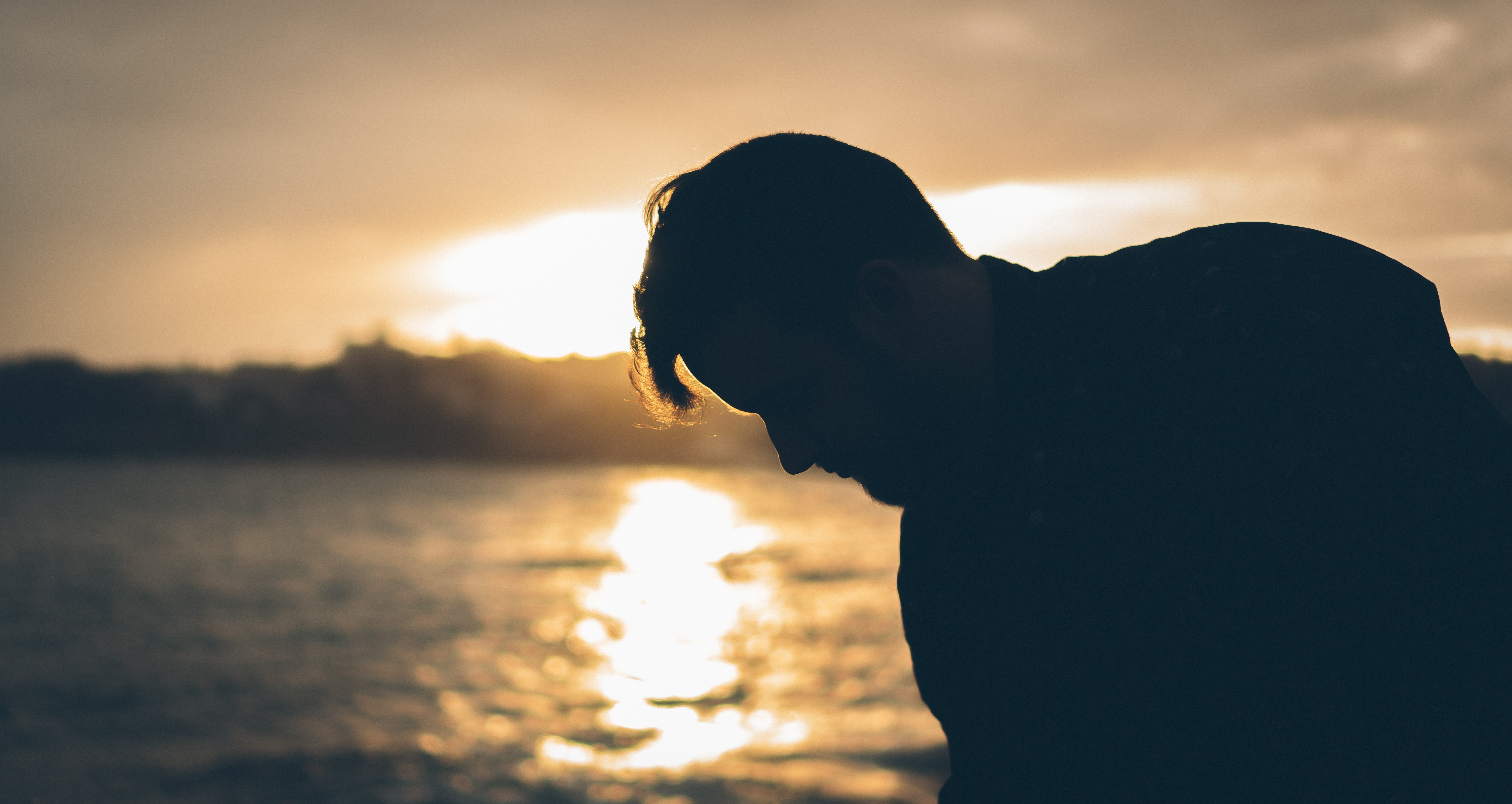 man standing near body of water during sunset
