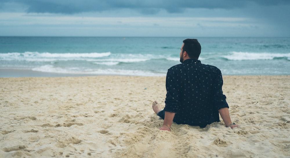 man sitting on beach sand