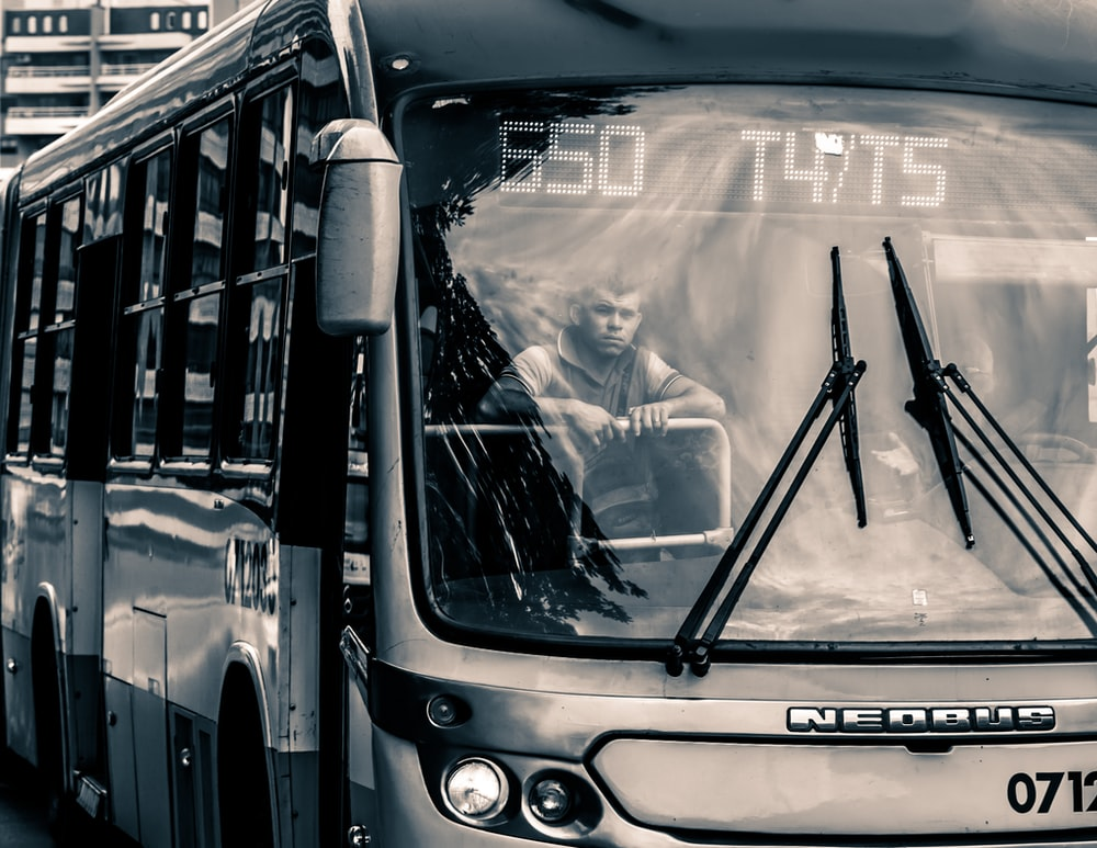 grayscale photo of man inside bus
