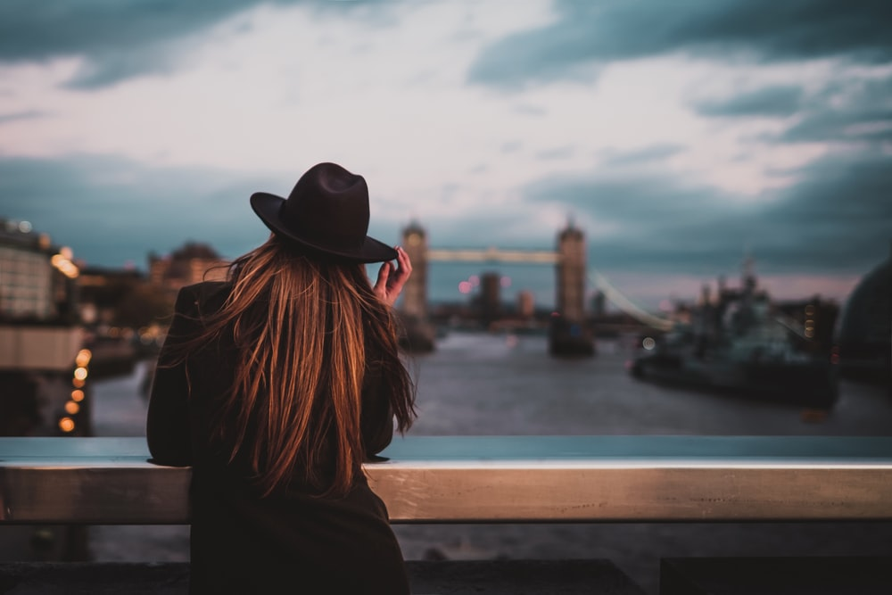selective focus photo of back of woman wearing fedora hat with elbows on railings facing bridge