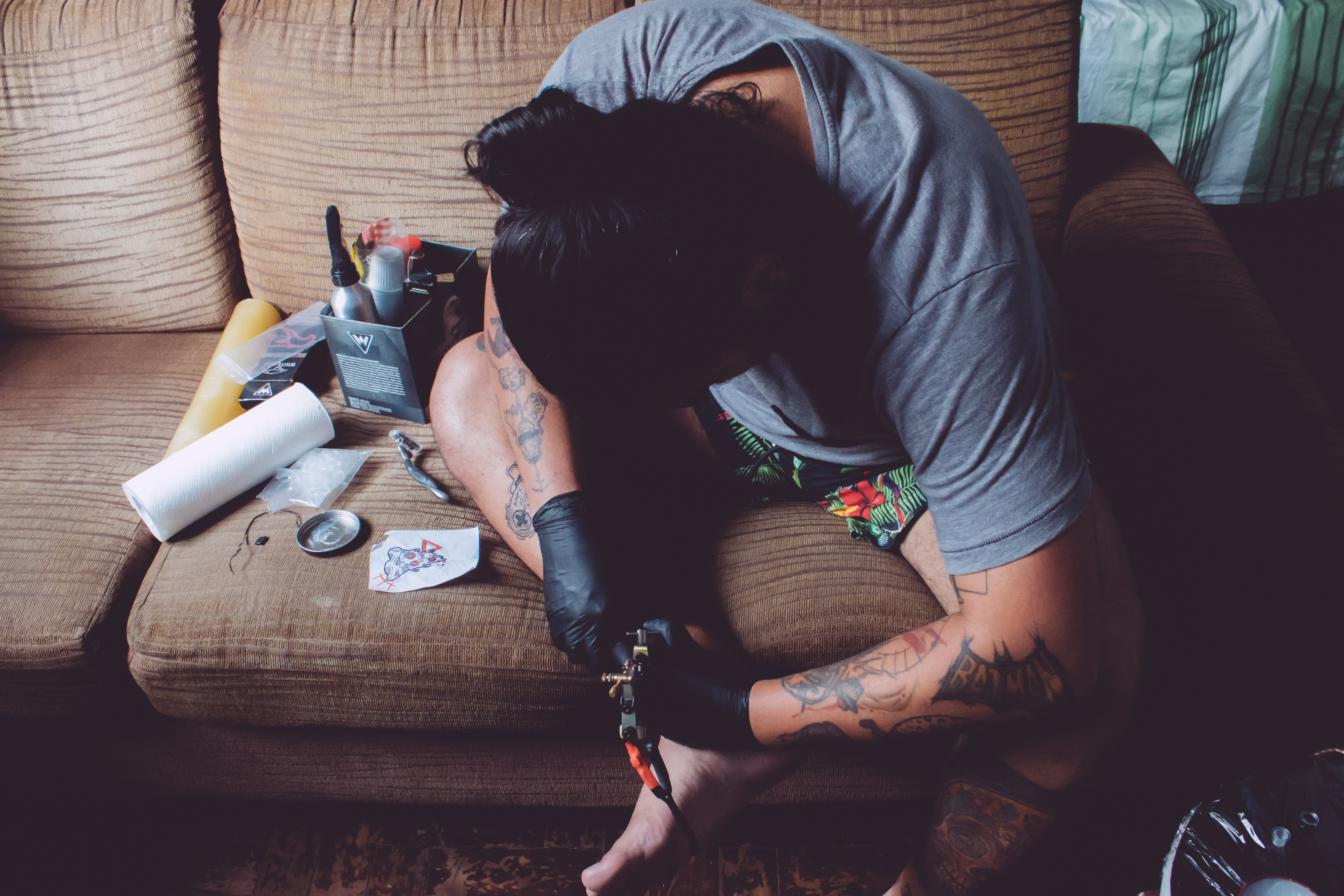man sitting on couch doing tattoo session