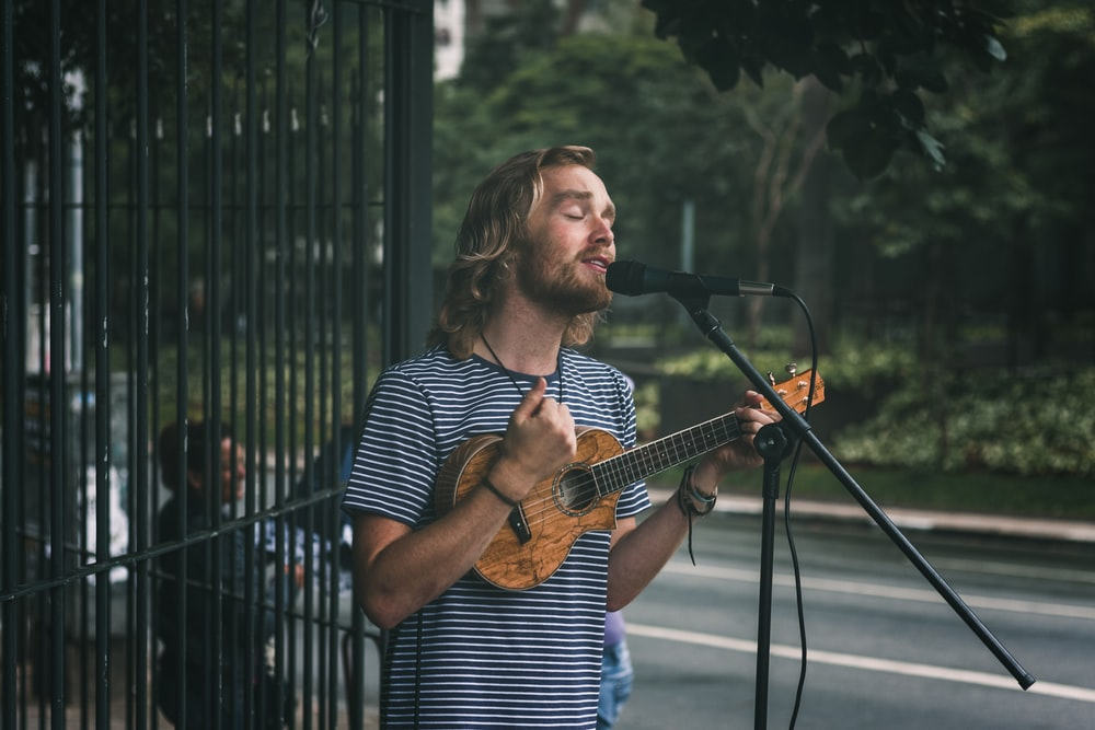 man holding ukulele standing near grills