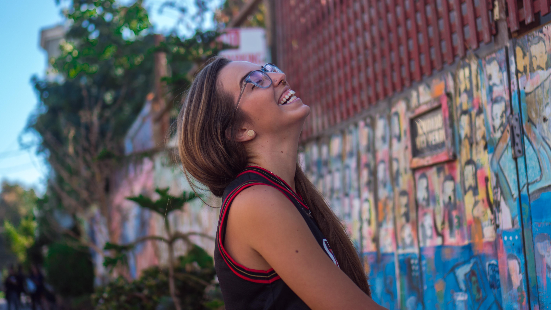 woman smiling facing wall