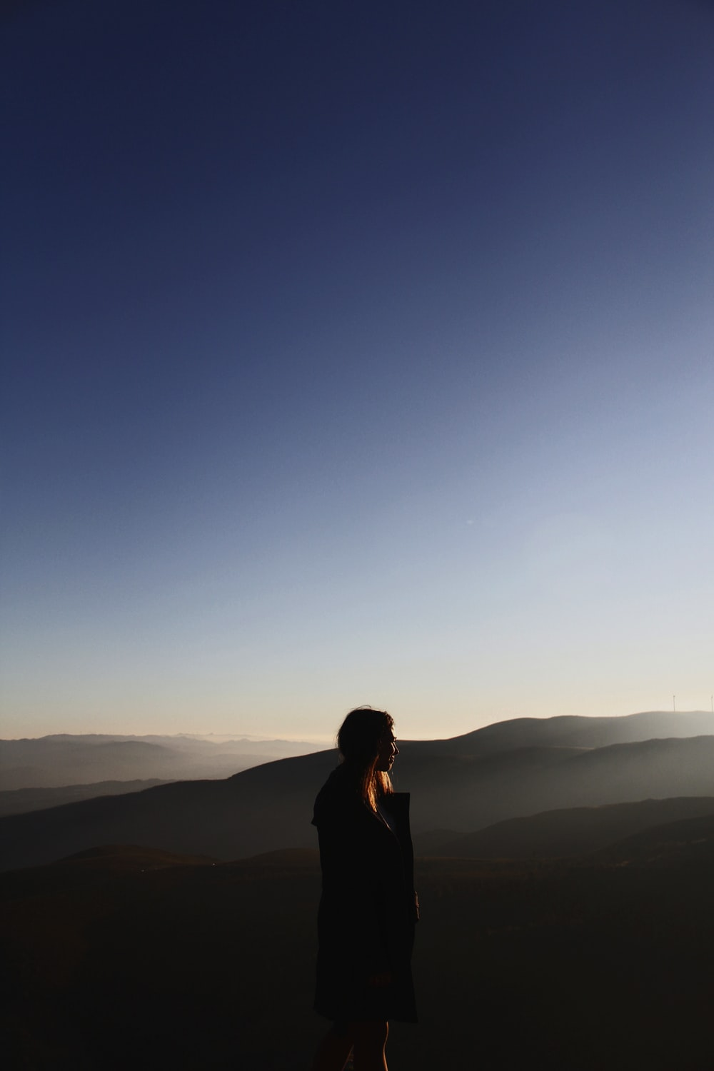 side view of woman on mountain under blue sky