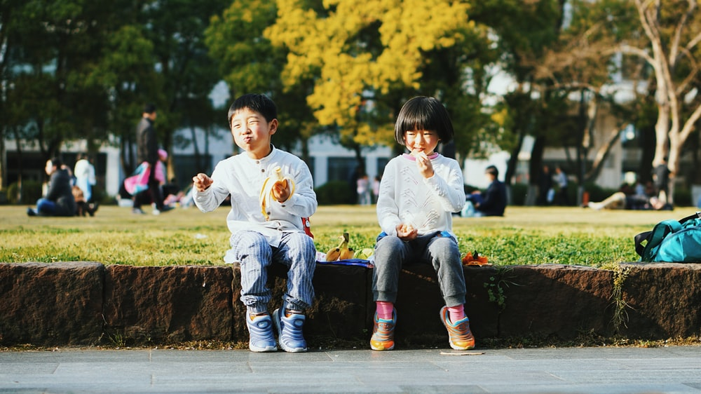 two kids sitting on brown stone