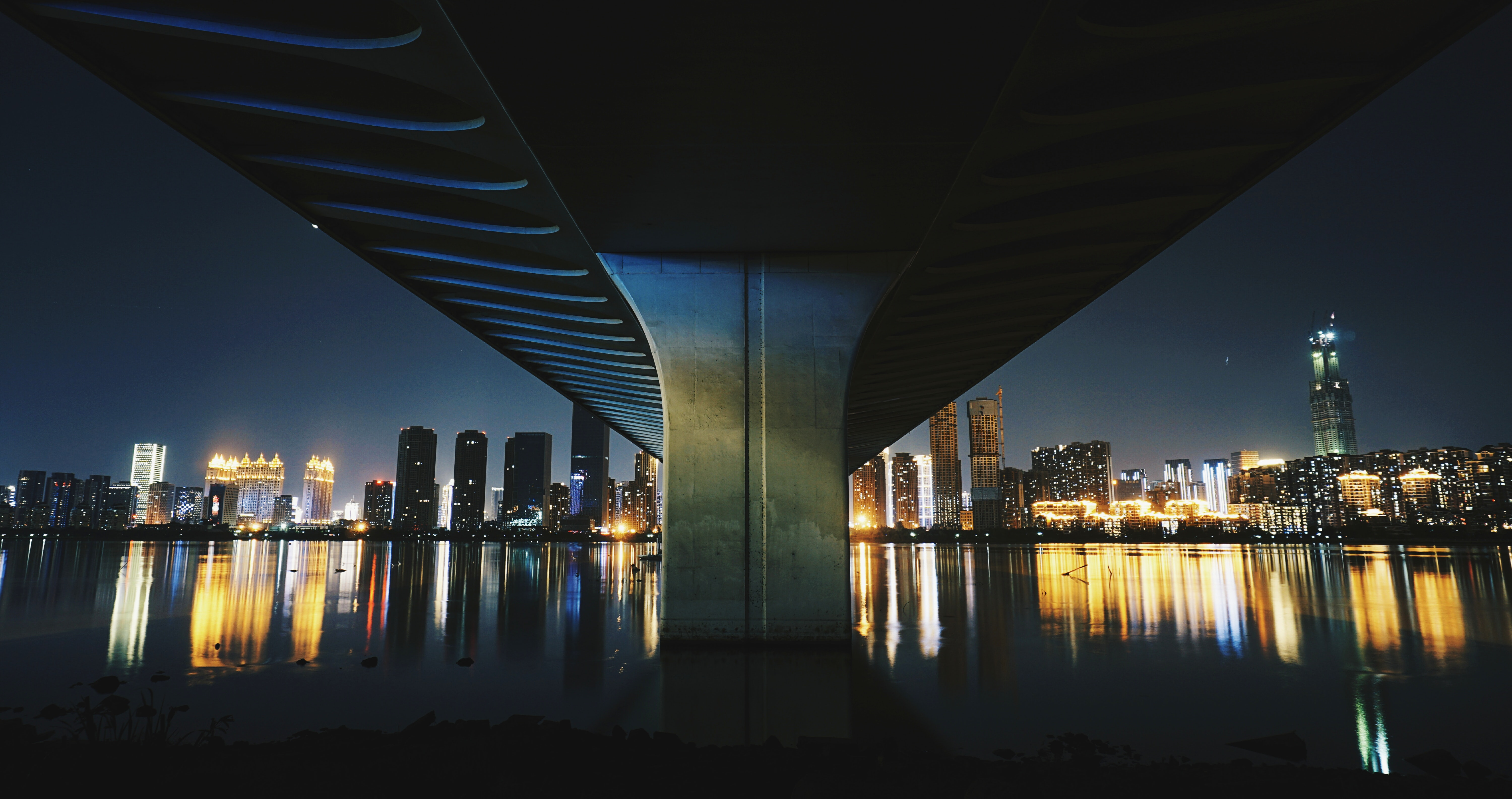 gray concrete bridge between city skyline during night time
