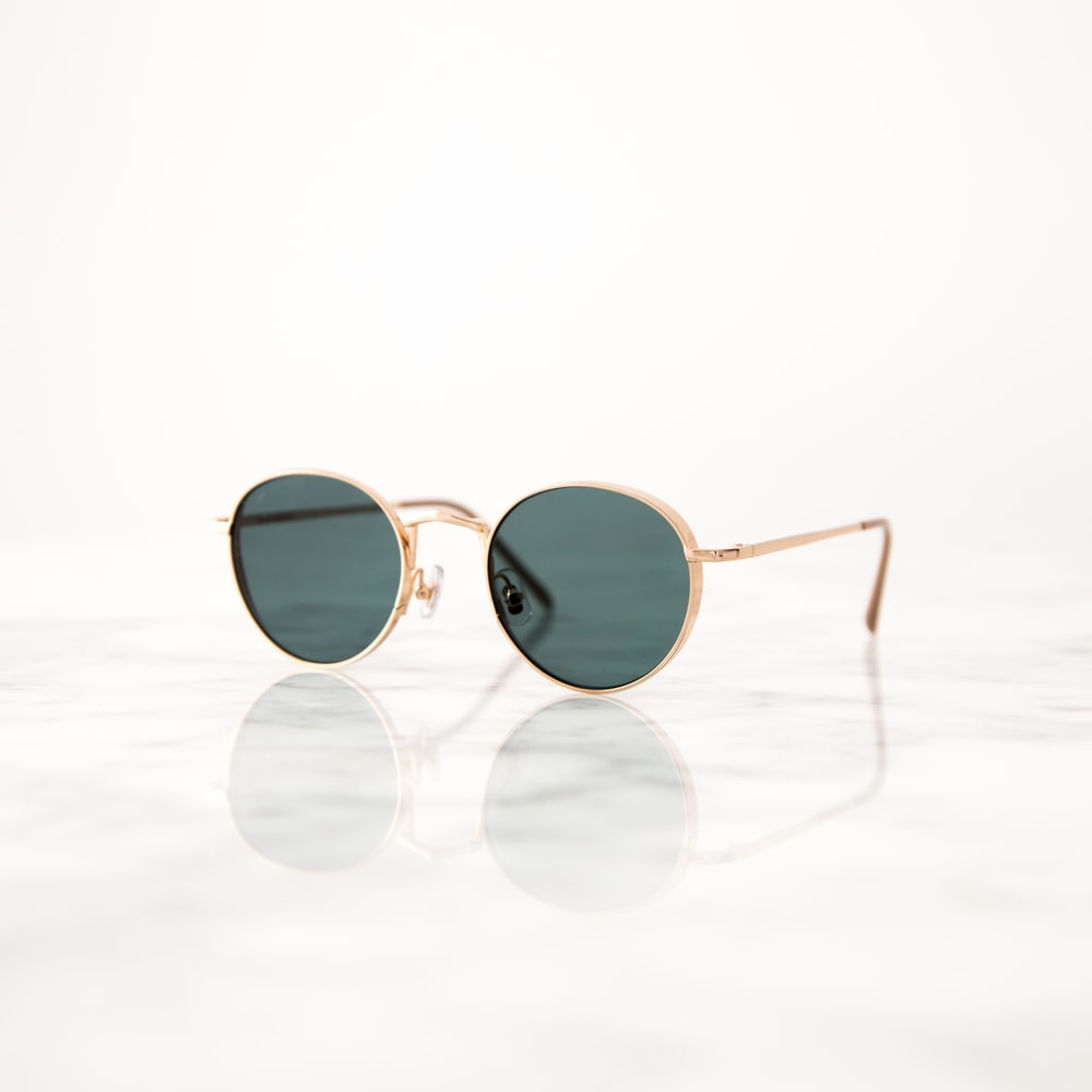 gold-colored framed hippie sunglasses on white surface