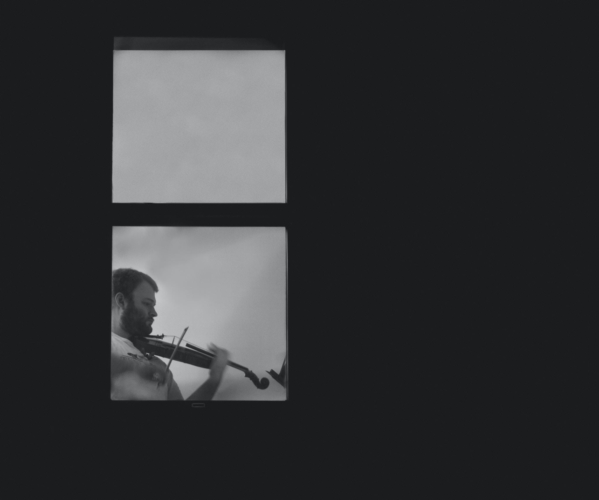 man playing violin near glass window