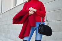 woman in red sweater beside white wall