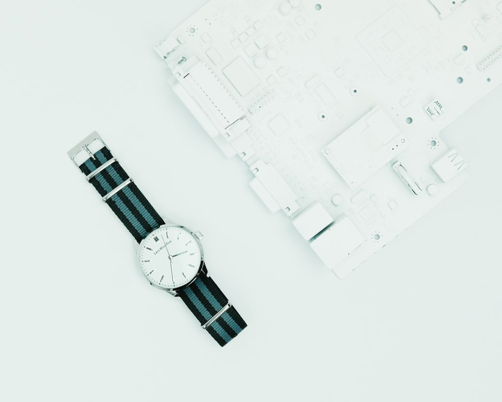 round silver-colored analog watch with black band
