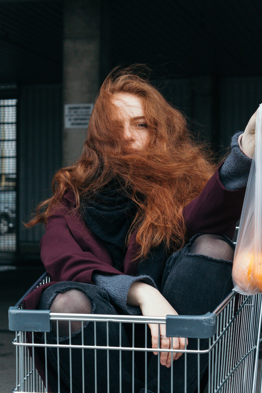 woman sitting on gray shopping cart