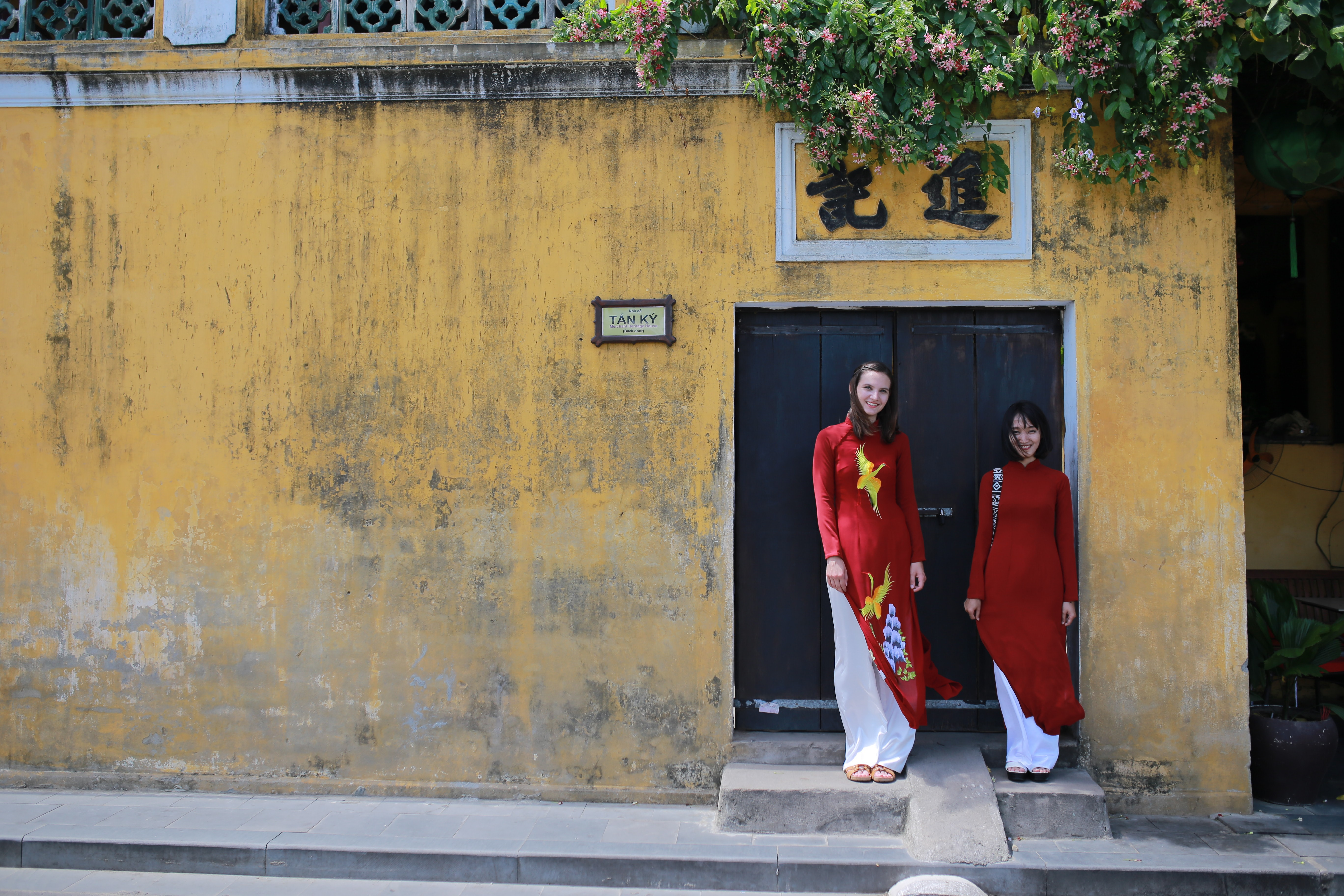 two woman standing in front of black gate