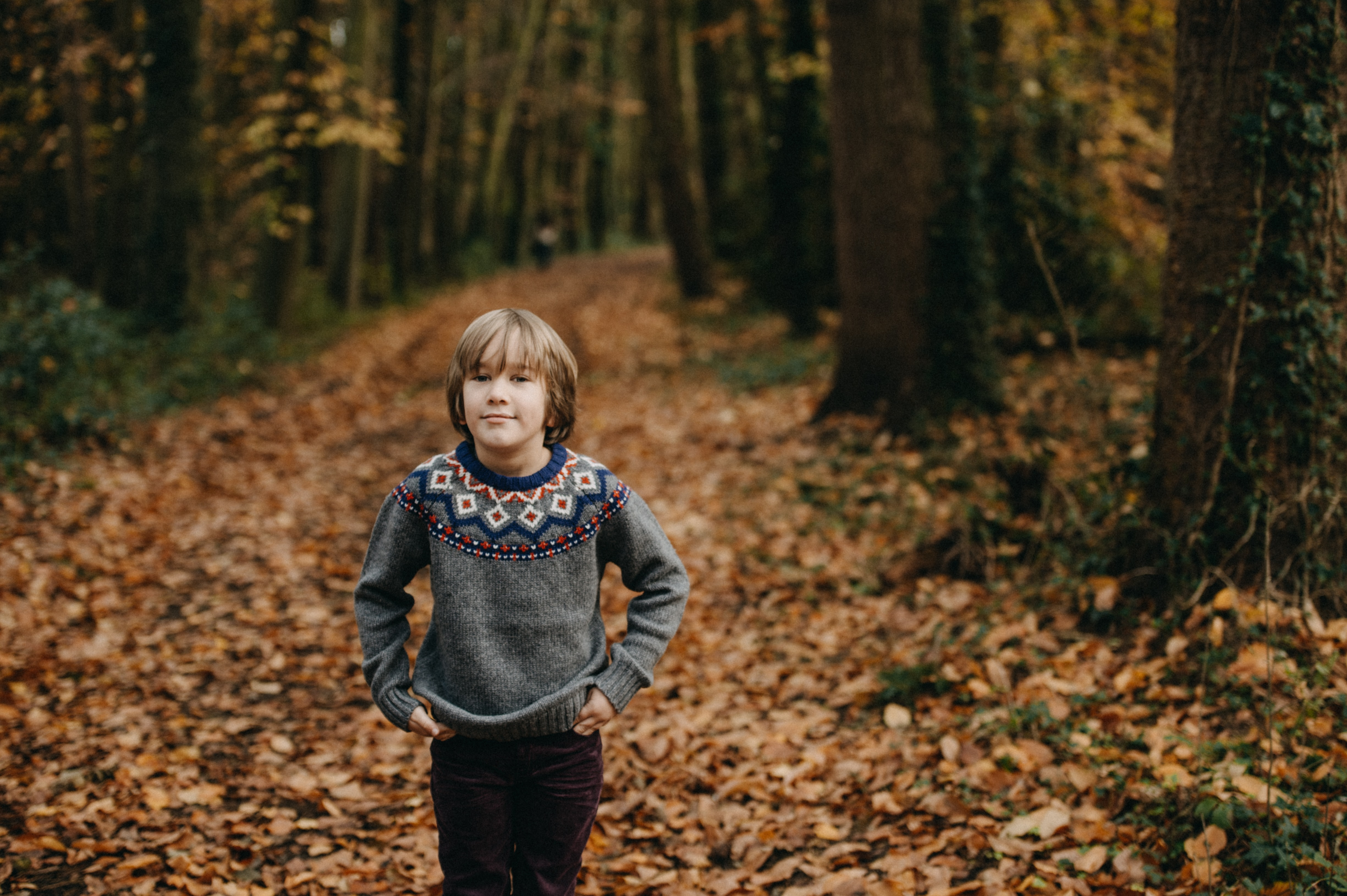 boy standing between tall trees