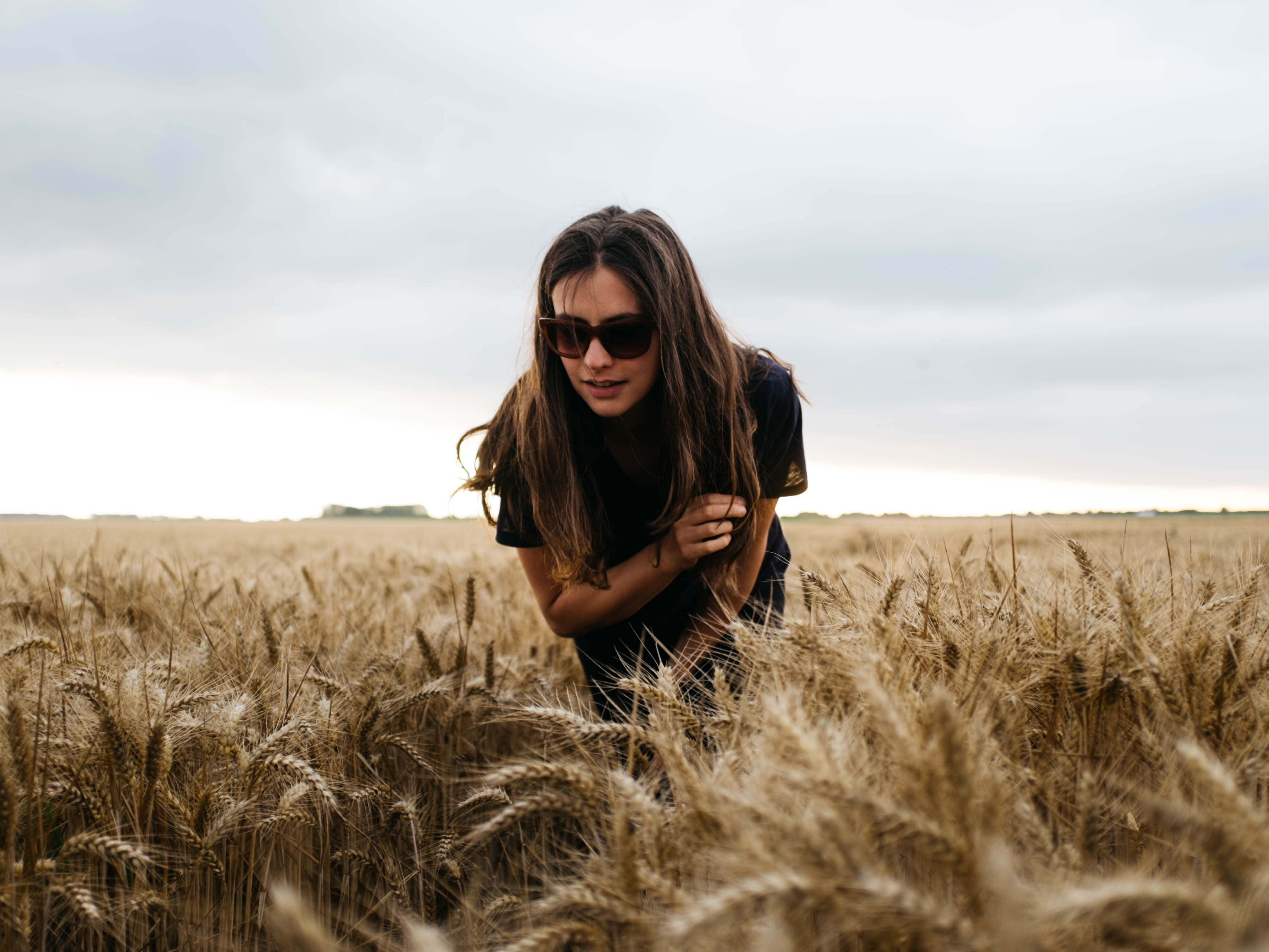 woman crotching brown grass field