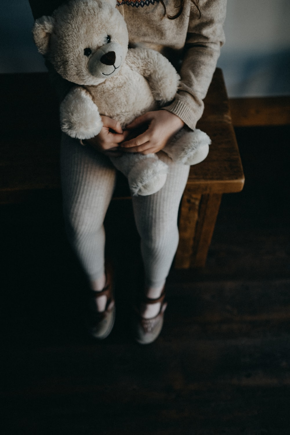 girl holding bear while sitting on bench