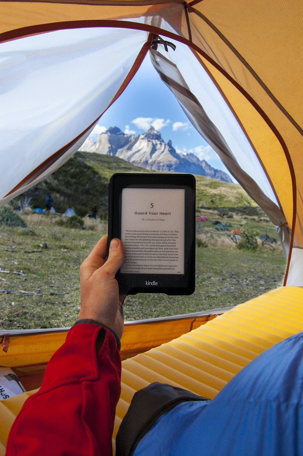person holding black Amazon Kindle E-Book reader inside tent at daytime