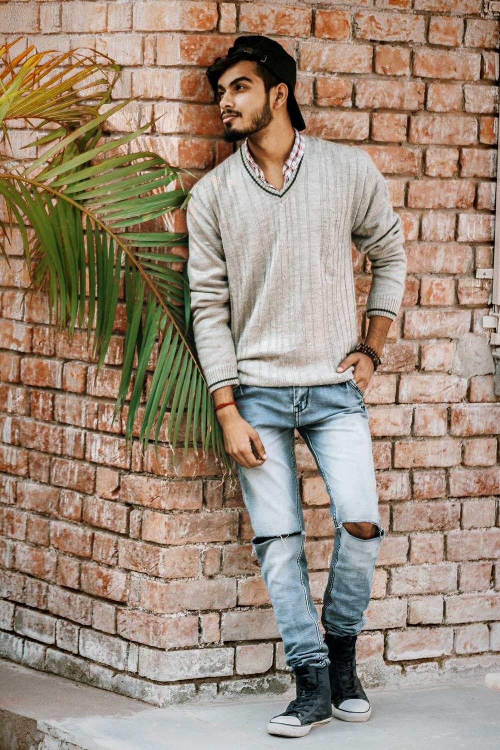 man leaning against on brick wall