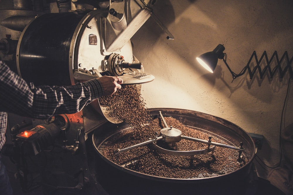 person pouring coffee beans on a machine