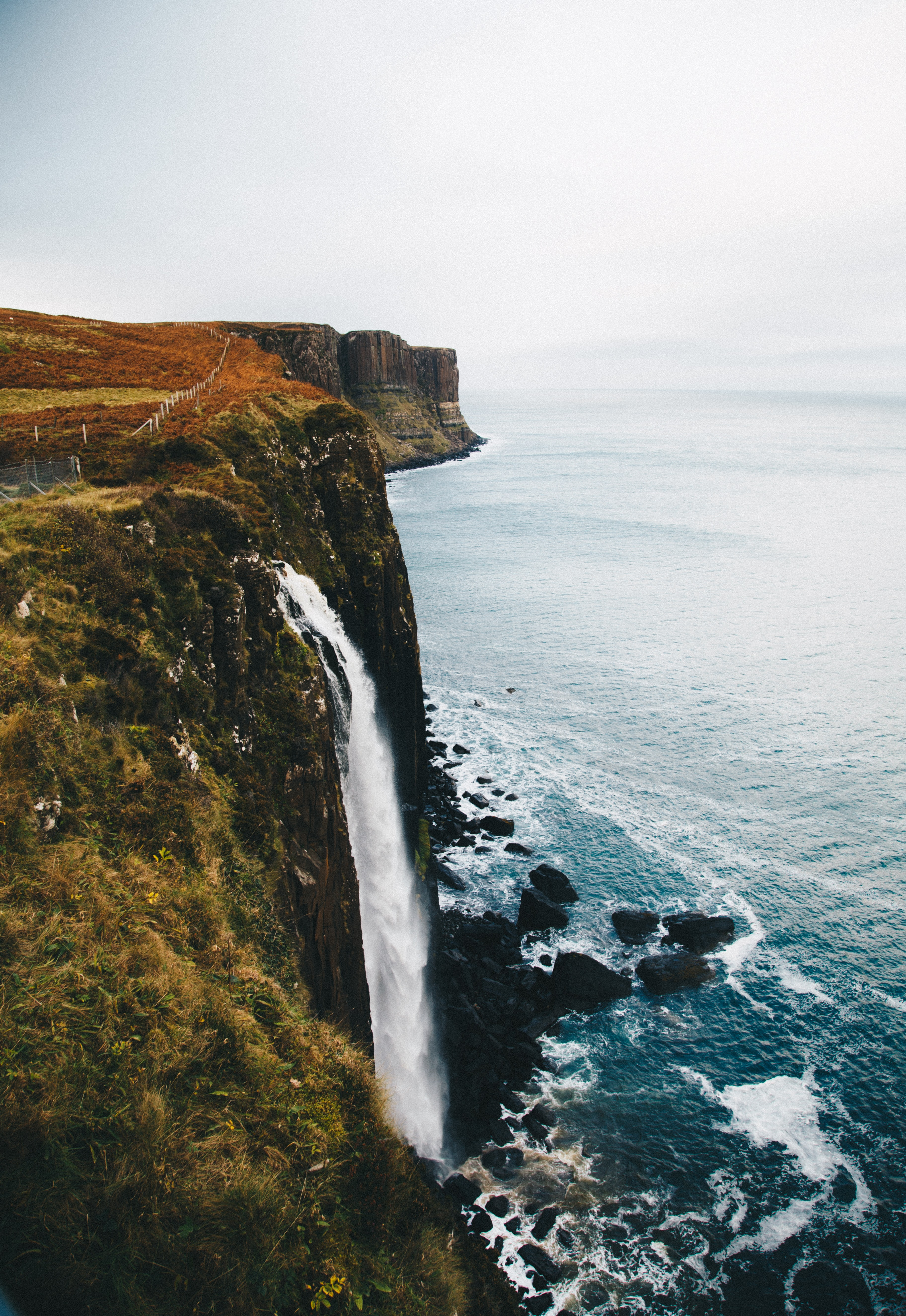 waterfalls in the cliff leading towards the ocean at daytime