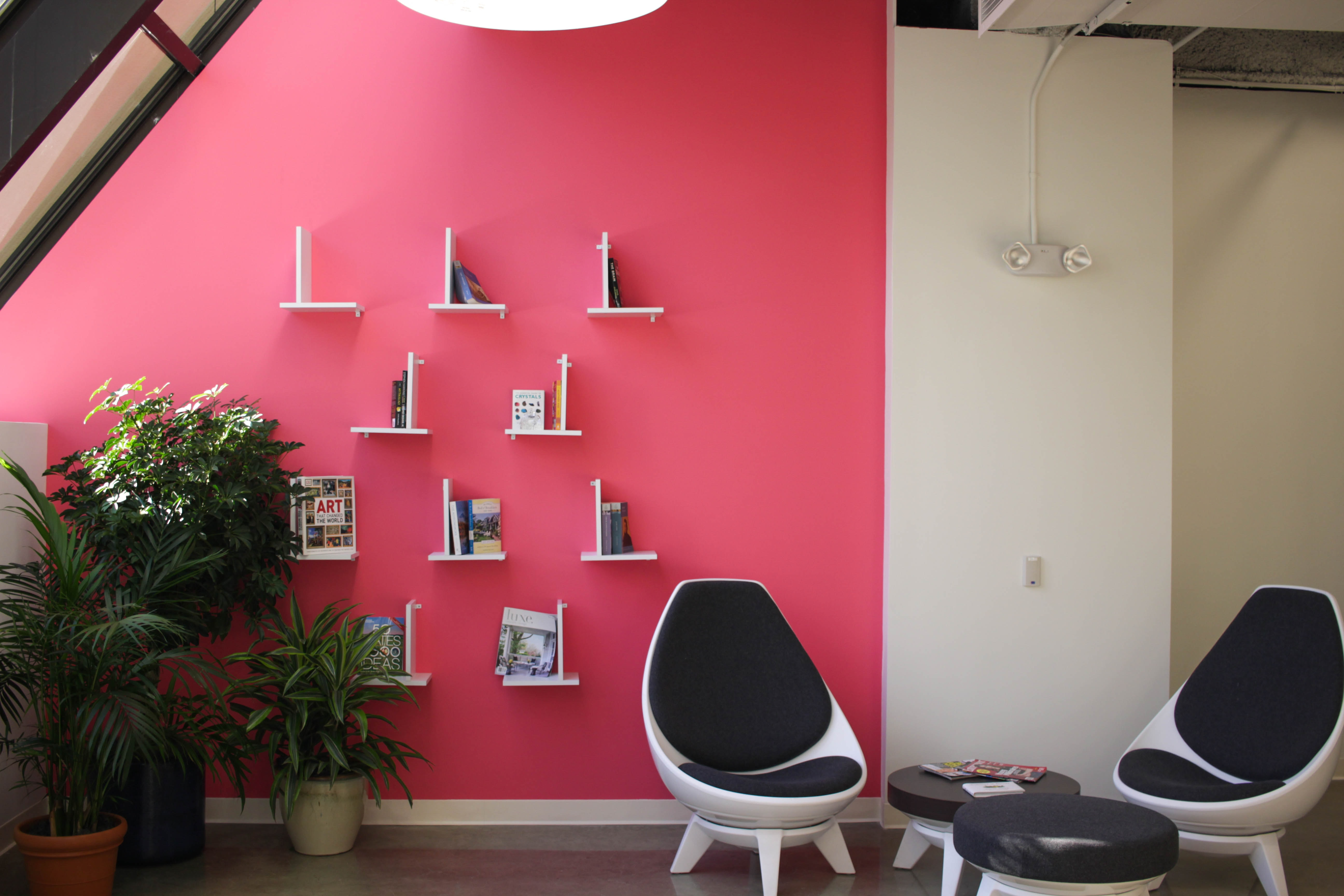 two white-and-black chairs near pink painted wall