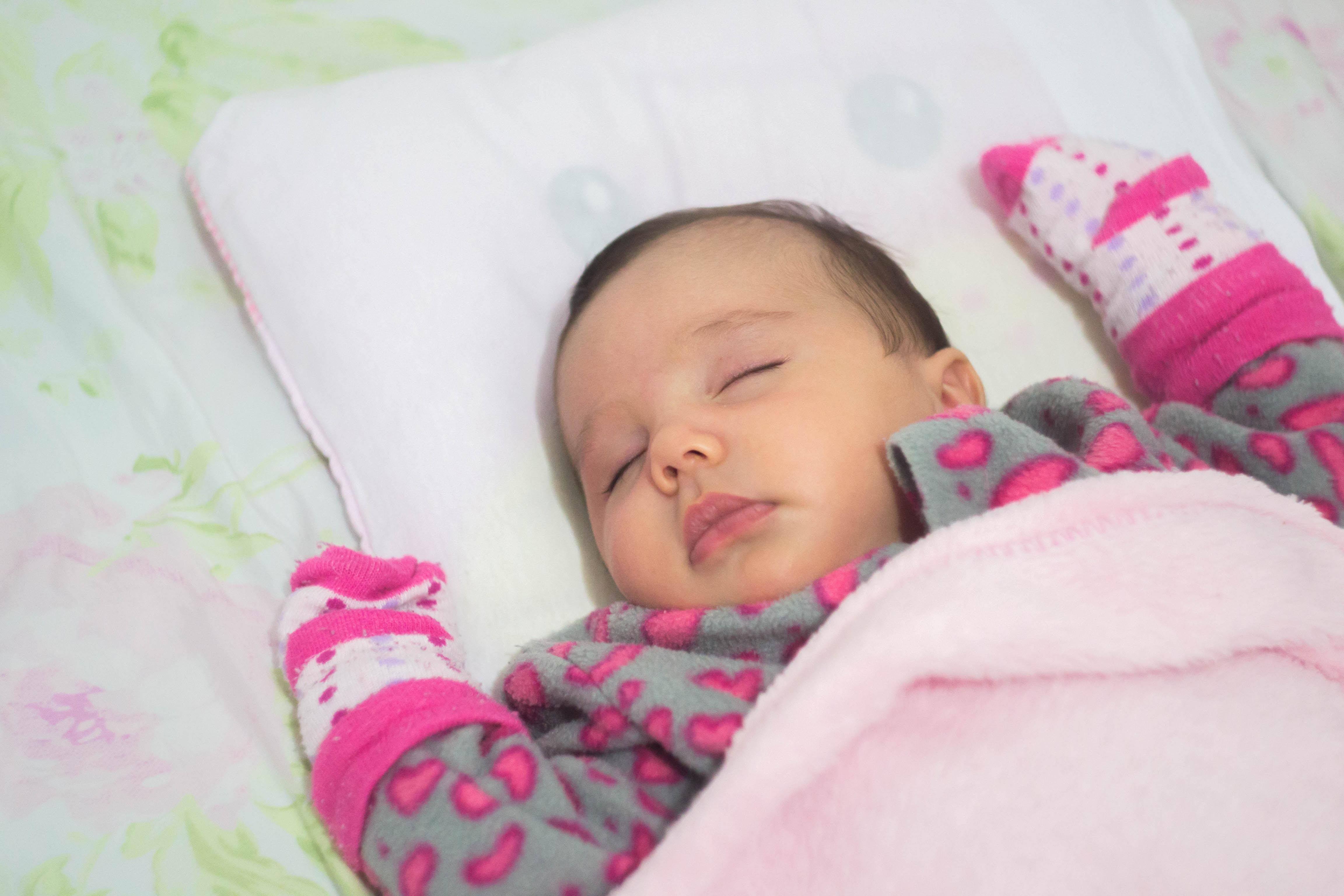 baby sleeping on white mat