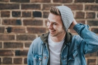 man holding the back of his head while smiling near brick wall