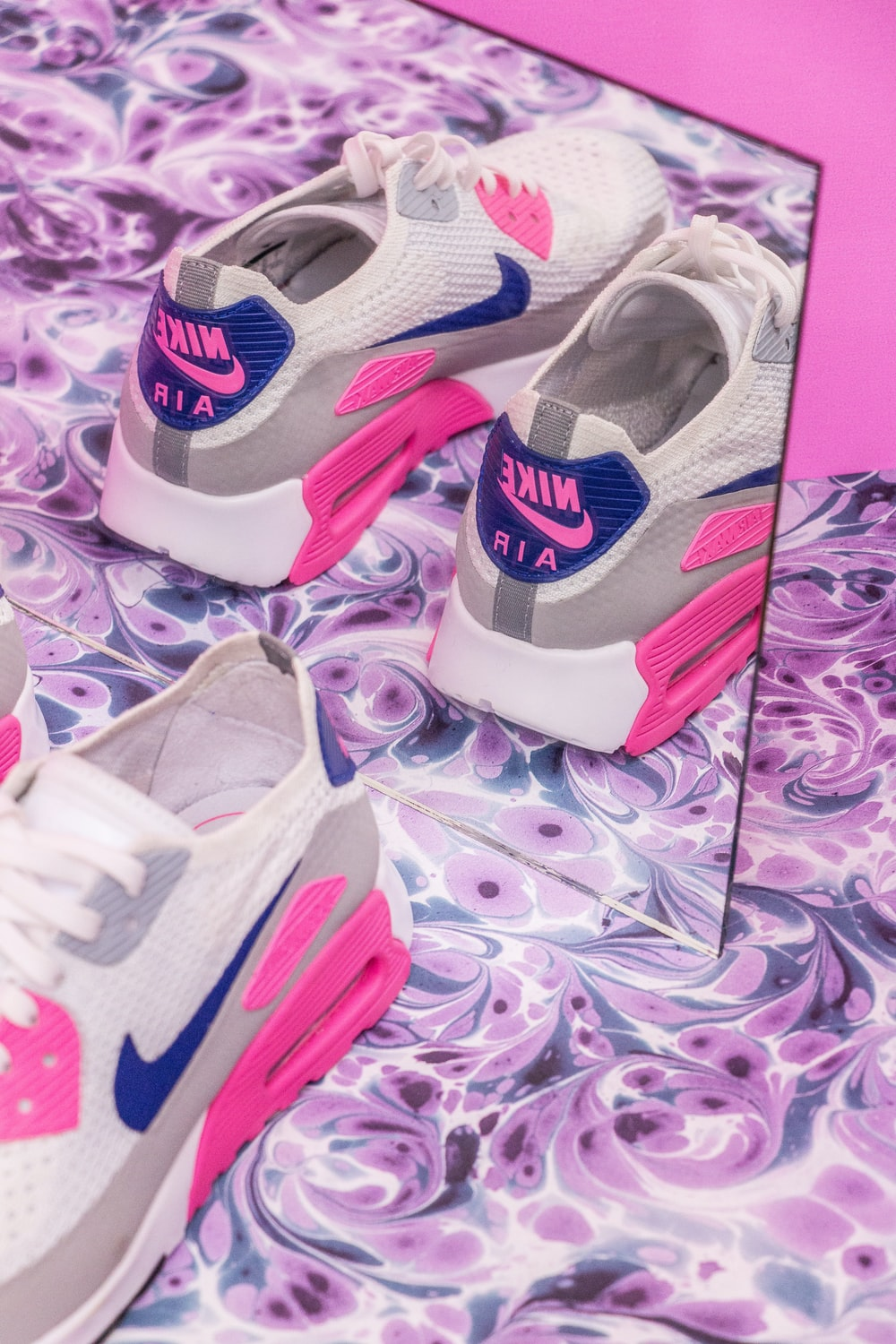 closeup photo pair of white-gray-and-pink Nike Air Max sneakers in front of mirror