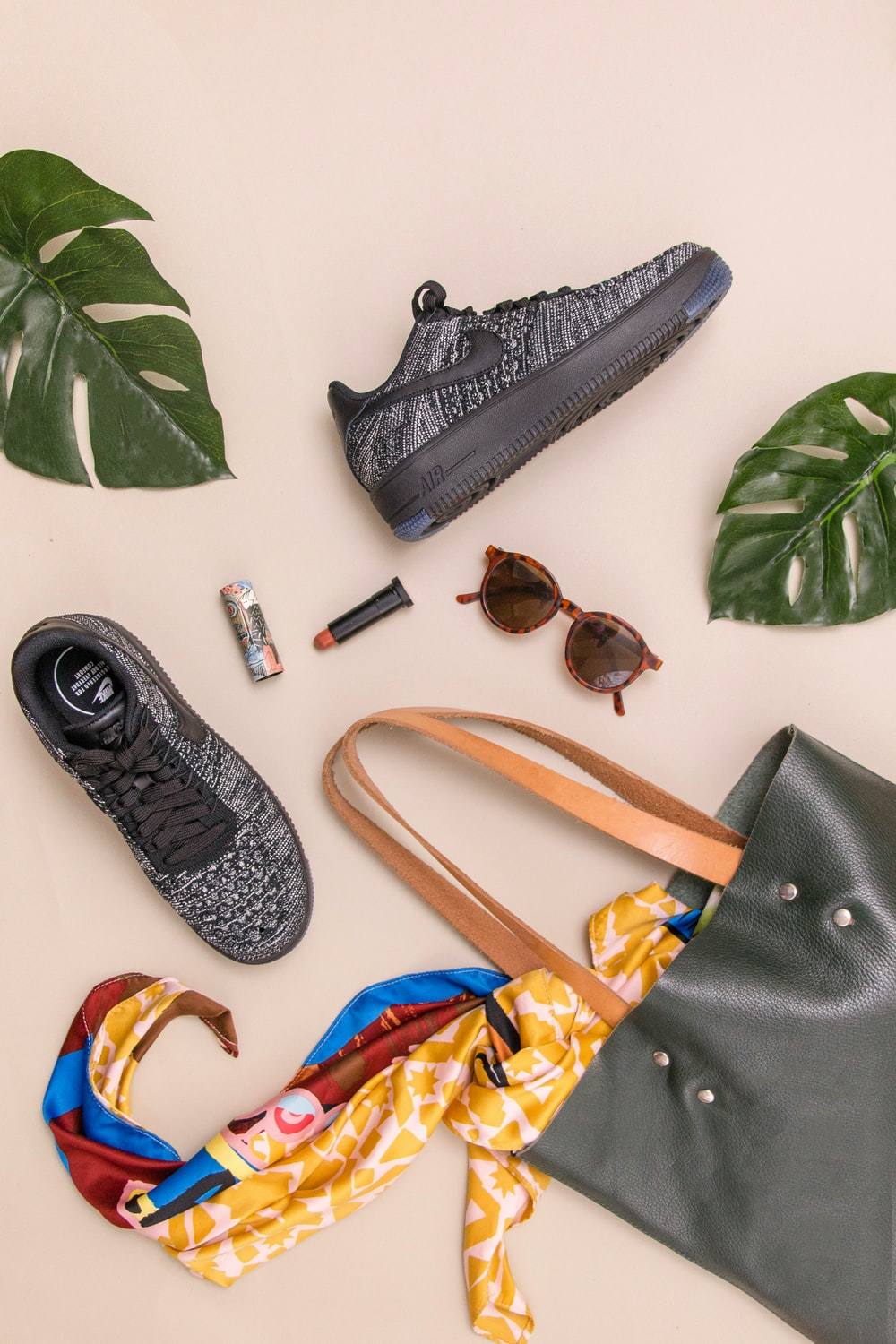 photo of bag, sneakers, and sunglasses on beige surface