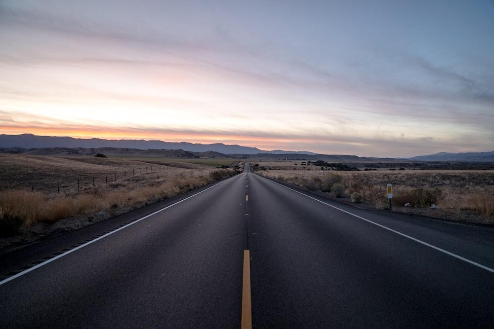 black concrete road between steppe