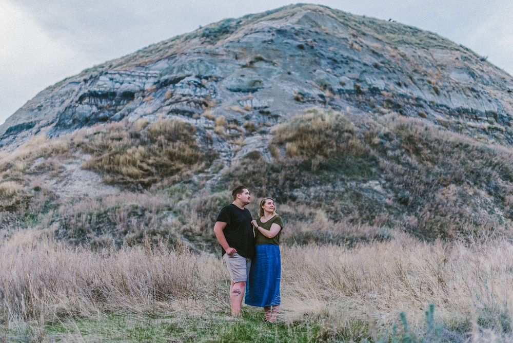 man and woman standing near mountain