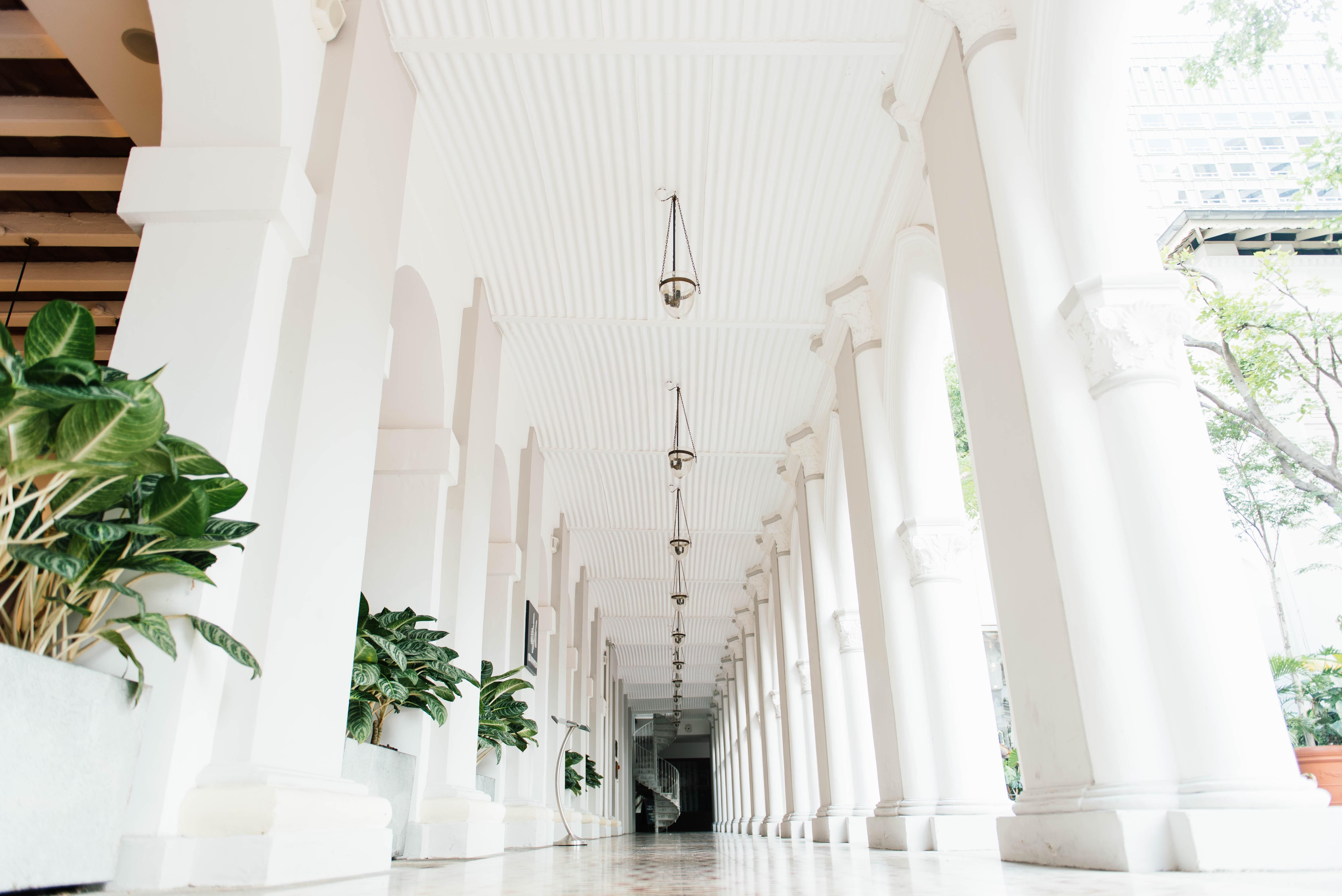 white ceramic tiles on hallway with pillars