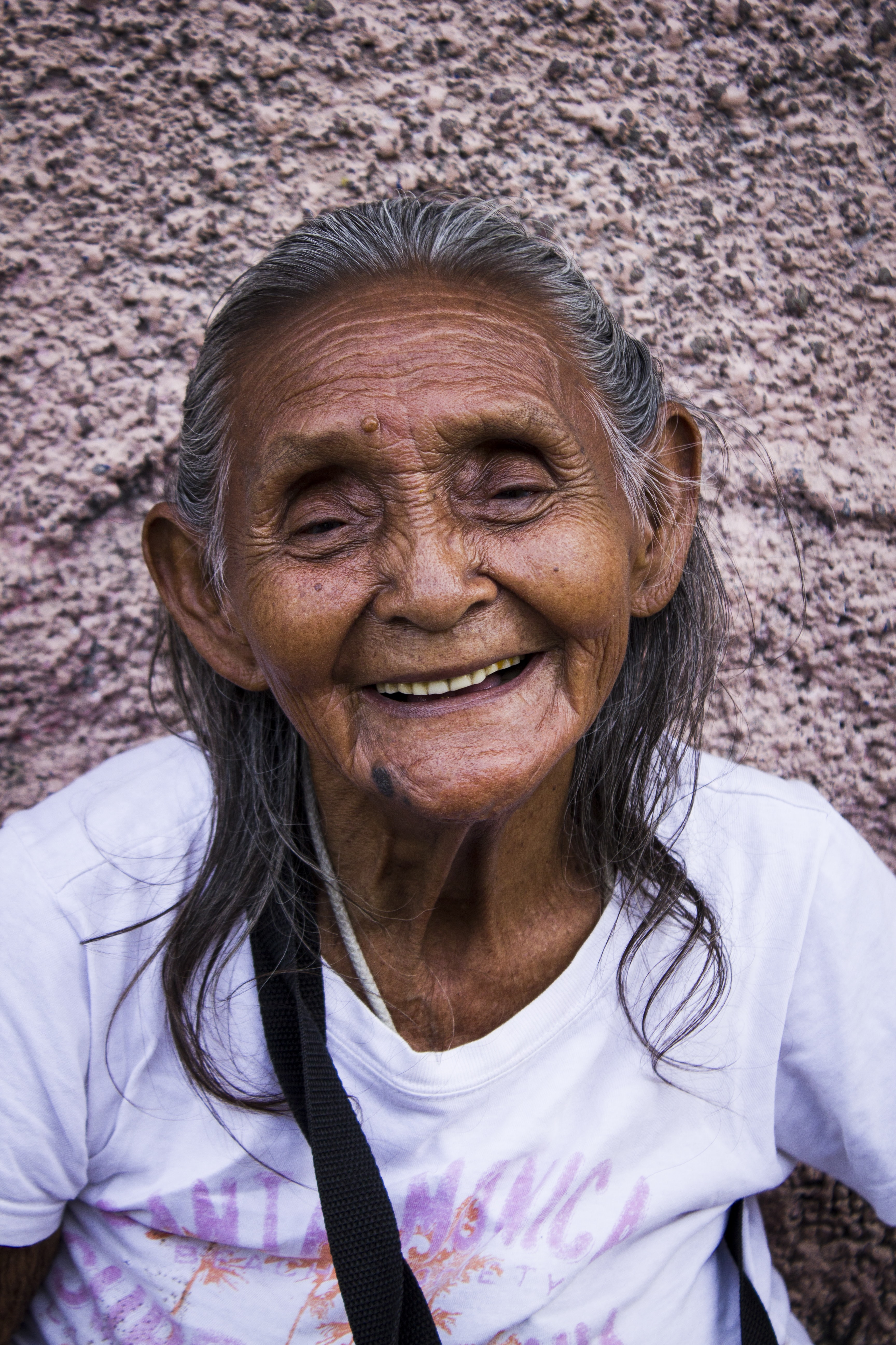 woman smiling while leaning on gray wall