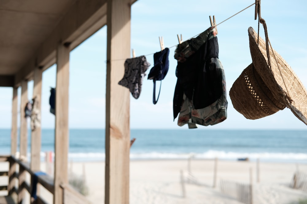 three clothes and hat hang on the rope