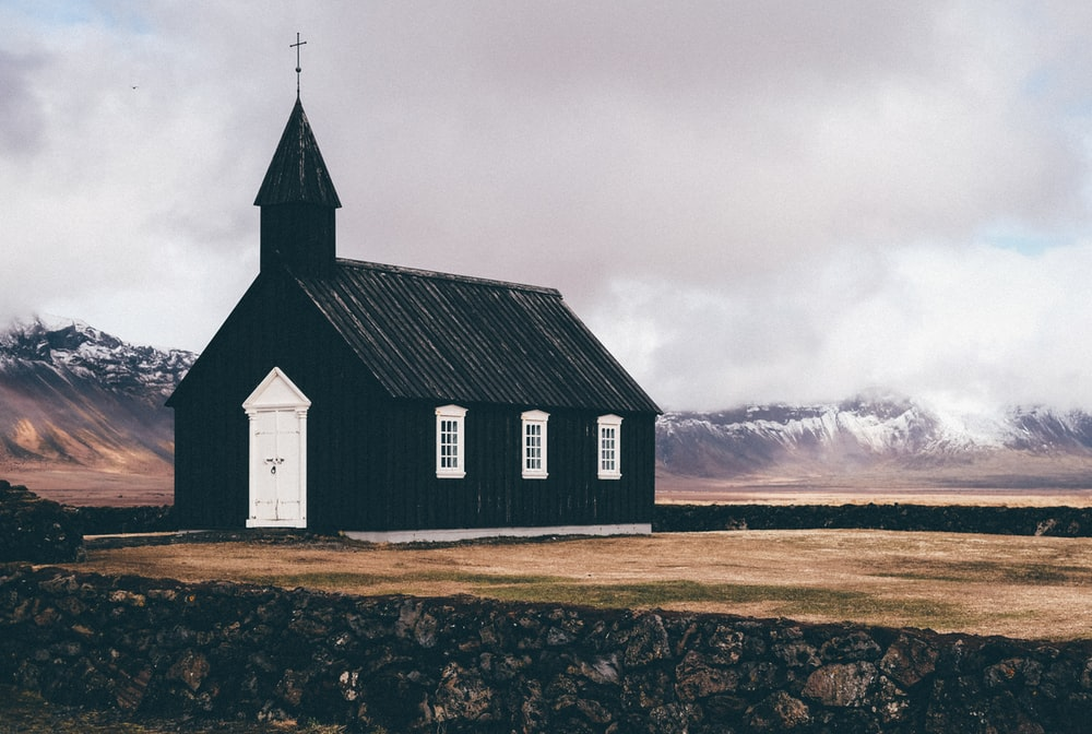 black and white church near open field background of mountain view