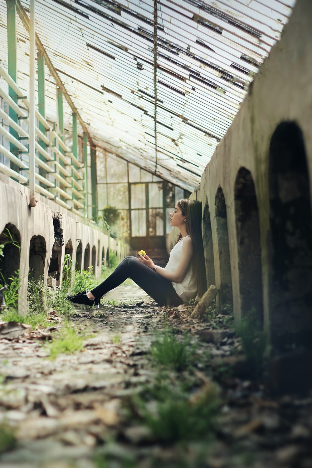 woman sitting between concrete fence at daytime