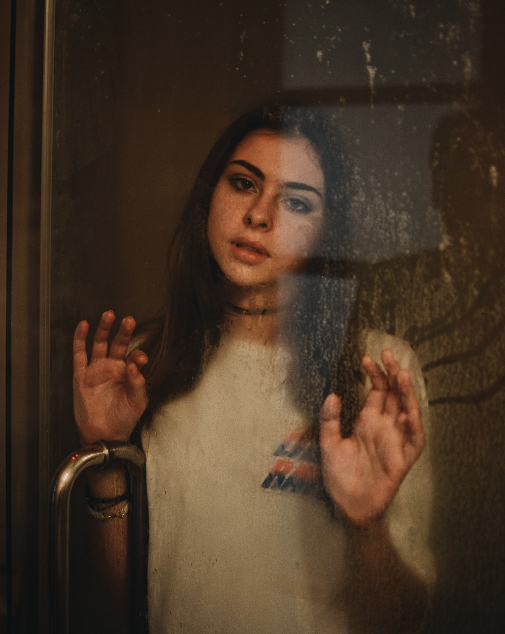 woman leaning on glass door
