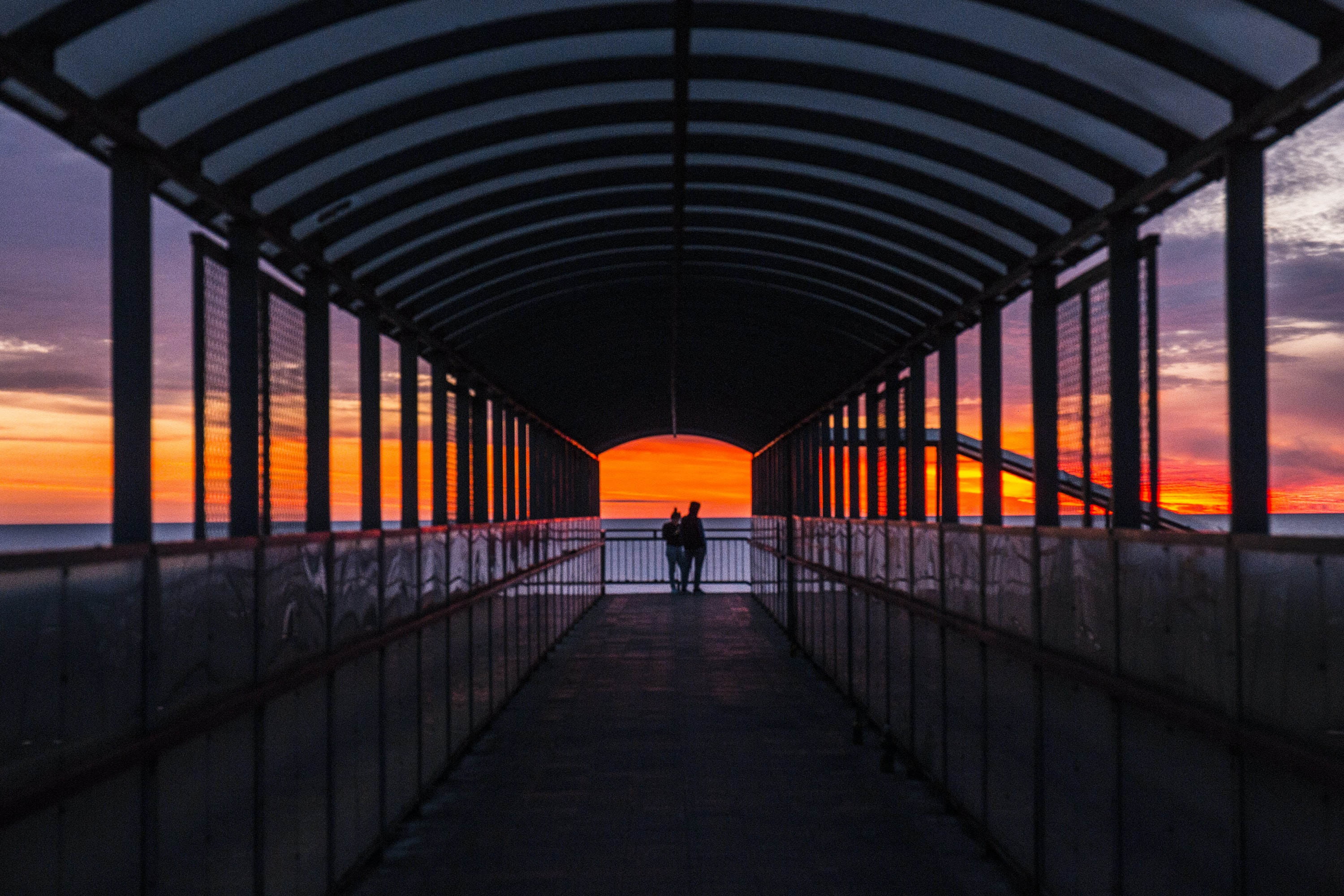 silhouette photo of persons on foot bridge