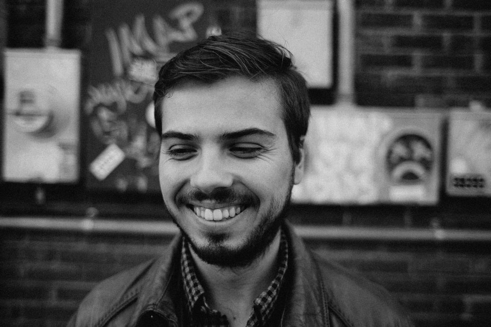 grayscale of man smiling