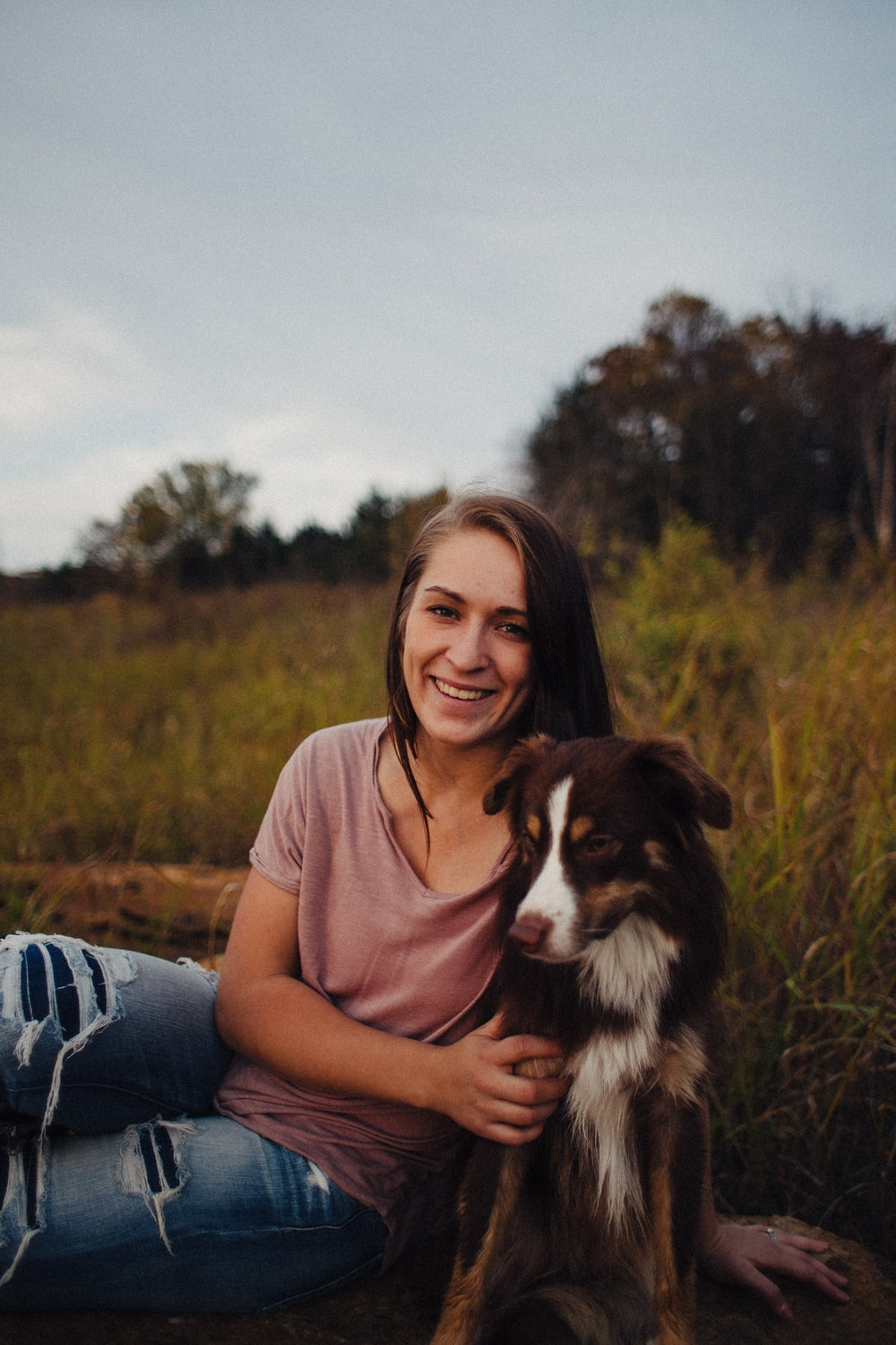 woman sitting beside a black and white dog