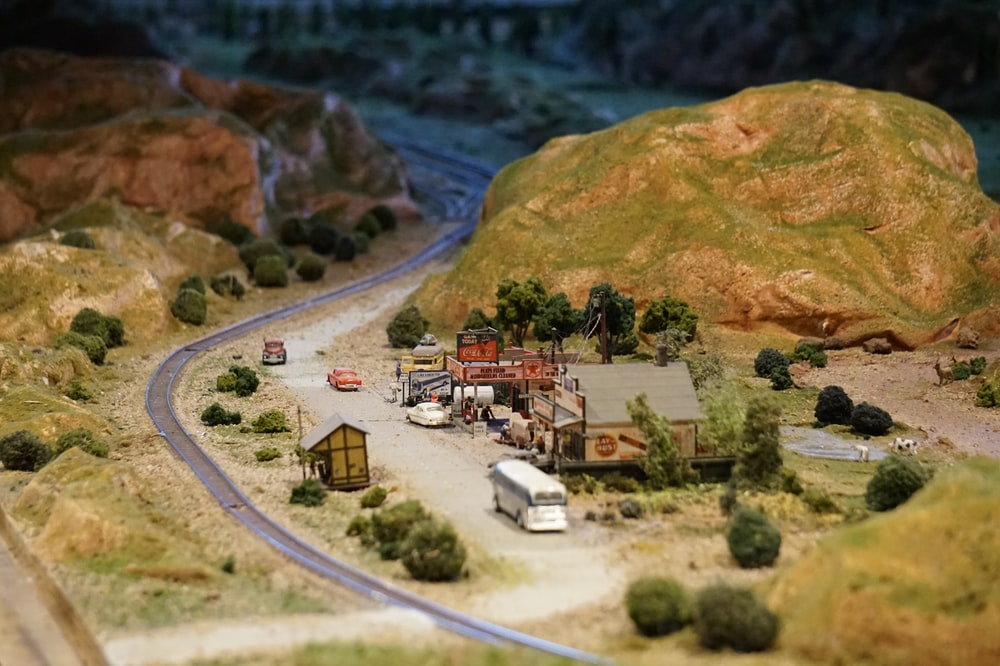 miniature town beside mountain and highway