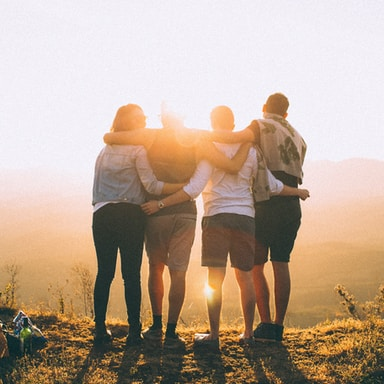 four person hands wrap around shoulders while looking at sunset