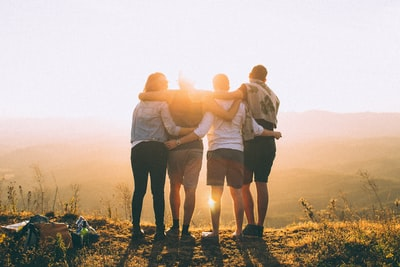 four person hands wrap around shoulders while looking at sunset friend teams background