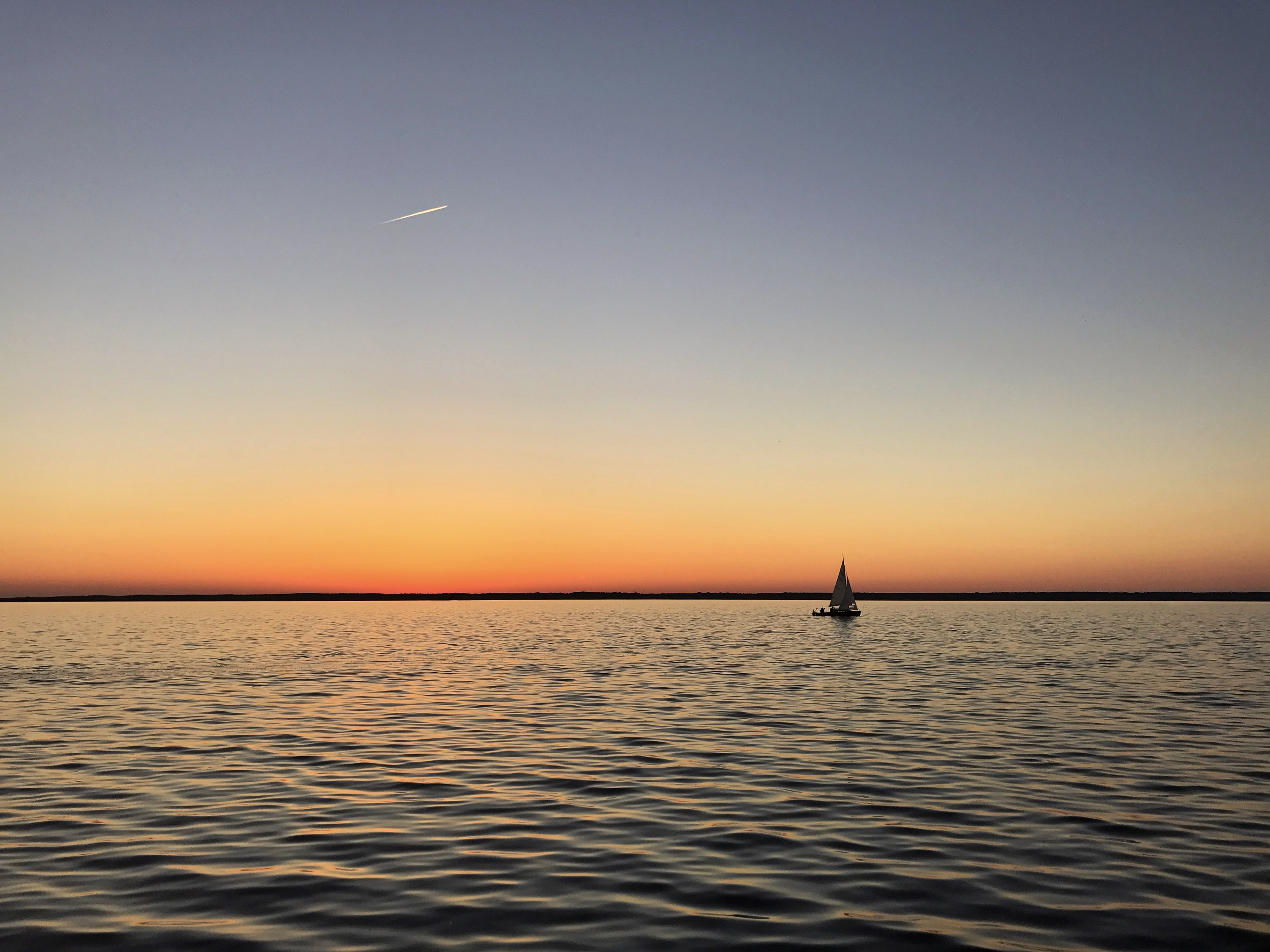 sail boat on calm body of water